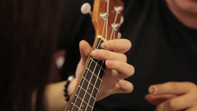 vídeos de stock e filmes b-roll de asian chinese male ukelele teacher teaching his partner to learn guitar at home - praticar