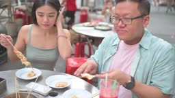 asian chinese male with disability sitting on wheelchair together female friend enjoying street food at petaling street