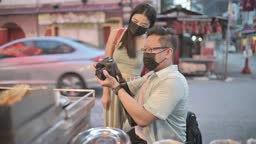 asian chinese male with disability sitting on wheelchair together female friend taking photo of enjoying street food at petaling street