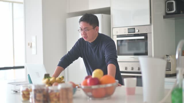 asian chinese male work from home using laptop video call  at kitchen counter - fruit bowl stock videos & royalty-free footage
