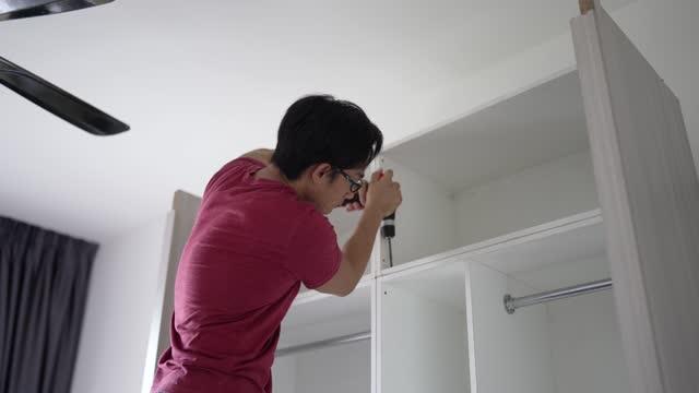 vidéos et rushes de homme chinois asiatique assemblant une armoire en bois à la maison - placard