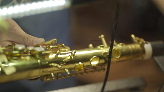 彼のワークショップでサックス音楽管楽器をチェックし、修復アジアの中国人の男 - 金管楽器点の映像素材/bロール