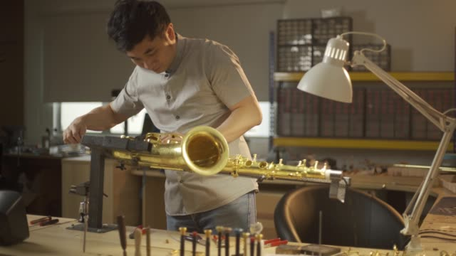 asian chinese man checking and repairing saxophone music wind instrument in his workshop - workbench stock videos & royalty-free footage