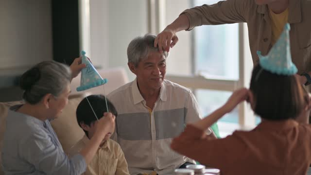 asian chinese man helping his father putting on wearing party hat getting ready celebrating birthday at home living room - party hat stock videos & royalty-free footage