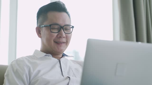 asian chinese man sitting on his sofa with cushion relaxing with his laptop surfing the net and shopping online - 僅一成熟男士 個影片檔及 b 捲影像