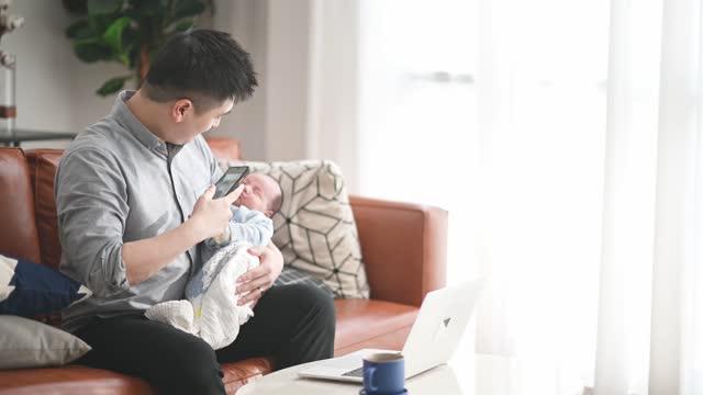 vídeos de stock, filmes e b-roll de homem chinês asiático trabalhando de casa na sala de estar enquanto carregava seu menino sentado no sofá - almofada
