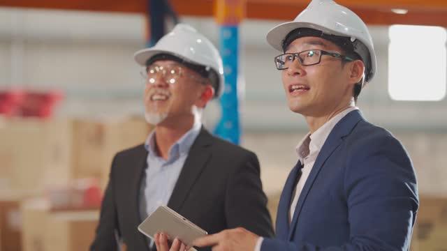Asiatische chinesische Management mit Diskussion im Lager mit weißen Hardhat mit digitalen Tablet