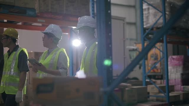 asiatische chinesische Management mit Lagerarbeiter im Lager mit weißen Hardhat mit digitalen Tablet diskutieren