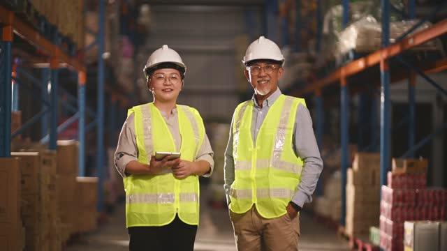 asiatische chinesische Management arbeiten Senior und Frau Blick auf die Kamera lächelnd auf Lagermitlager mit weißen Harthut Faltarme