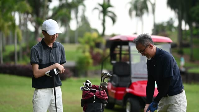 asian chinese mature adult selecting driver golf club from golf bag for tee off and guiding teaching his son at the golf course tee off point - golf bag stock videos & royalty-free footage