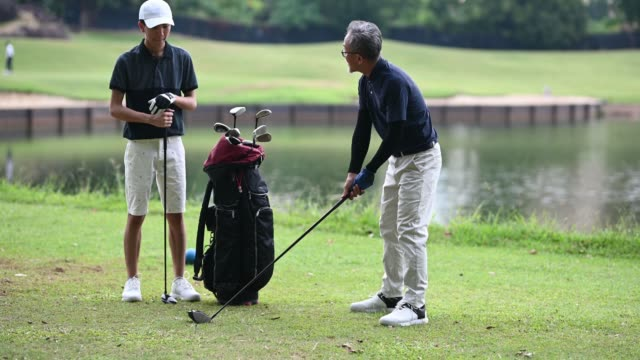 asian chinese mature adult selecting driver golf club from golf bag for tee off and guiding teaching his son at the golf course tee off point - golfer stock videos & royalty-free footage