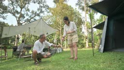 asian chinese mature couple setting up tent and camp at woodland