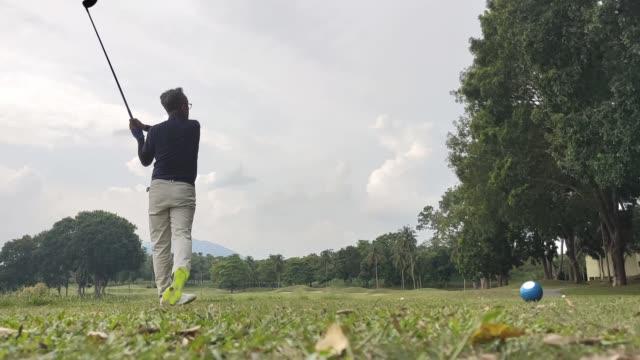 アジアの中国の成熟した男は週末にティーオフポイントゴルフコースで彼のドライバークラブをスイングオフ - ゴルフシューズ点の映像素材/bロール