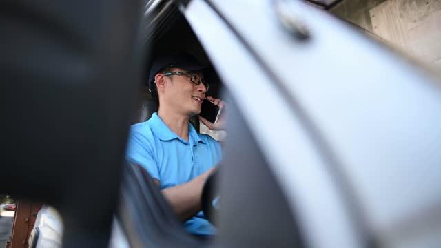 アジアの中国の成熟した男性配達人は、配達バンの中の運転席で電話を使用して顧客と通信する - 中年の男性一人点の映像素材/bロール