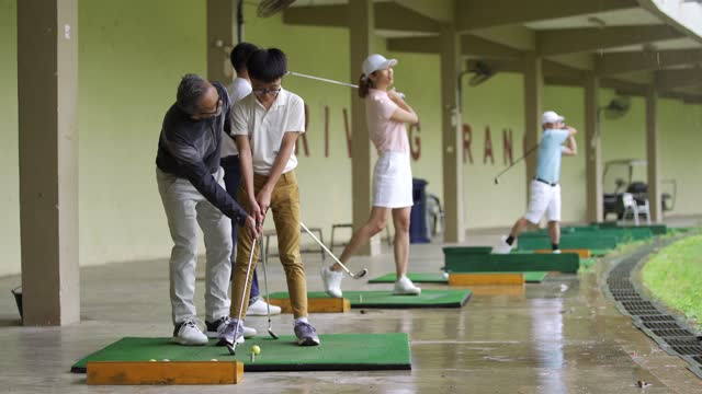 asian chinese mature man golf couch teaching young male student to play golf at driving range - driving range stock videos & royalty-free footage