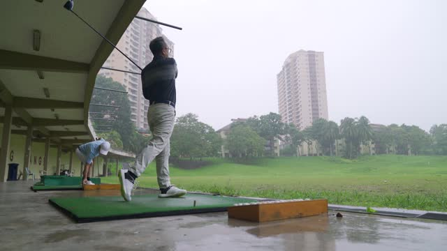 asian chinese mature man golfer playing golf at driving range golf course - driving range stock videos & royalty-free footage