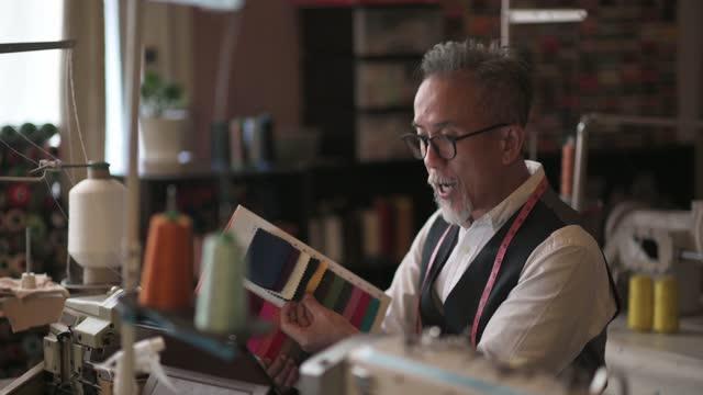 vídeos y material grabado en eventos de stock de asiático chino maduro hombre sastre con cara stubble videollamada con su cliente utilizando tableta digital explicando material de tela - textile