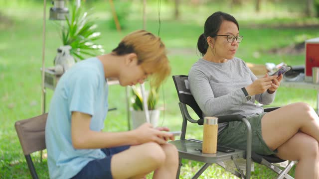 vídeos de stock, filmes e b-roll de mulher asiática chinesa madura com seu filho sentado usando telefone inteligente em tenda de acampamento durante o fim de semana - smart
