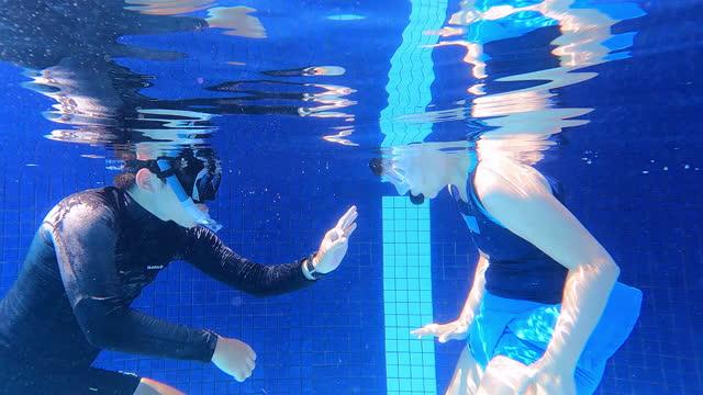 stockvideo's en b-roll-footage met aziatische chinese rijpe vrouw met scubamasker die het snorkelen ademhalingsoefening in het water met haar bus uitoefent - zwemvlies