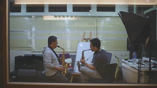 asian chinese mid adult man learning music instrument playing saxophone from his instructor in music studio - rehearsal stock videos & royalty-free footage