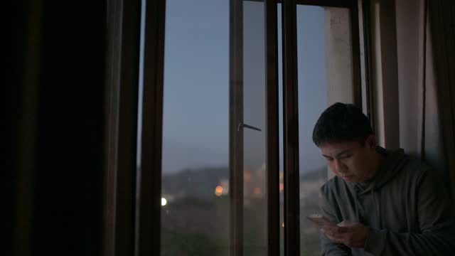 asian chinese mid adult man looking at smart phone from his home during sunset with serious facial expression with hooded shirt - scrolling stock videos & royalty-free footage