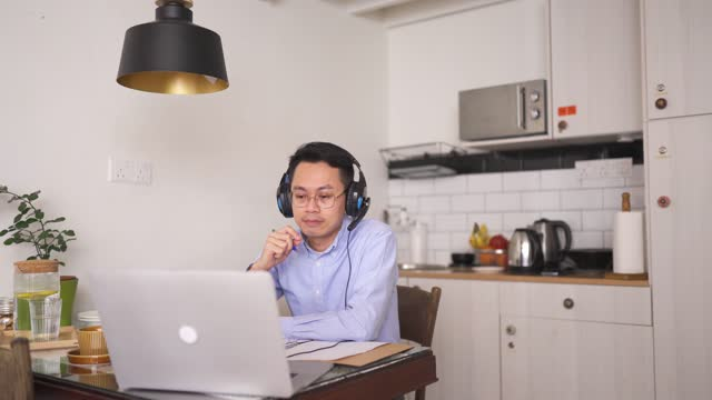 asian chinese mid adult man smiling attending online meeting using laptop at dining area with headphone headset - attending stock videos & royalty-free footage