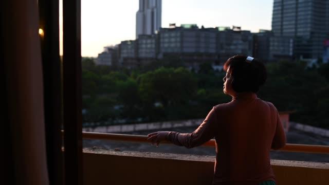 vídeos de stock, filmes e b-roll de asiática chinesa média mulher adulta ouvindo música em fones de ouvido sem fio ficar na varanda durante o pôr do sol - in silhouette