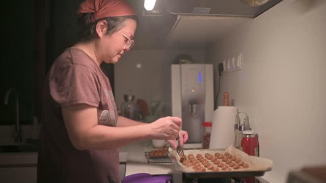 台所で自宅で焼いたピーナッツビスケットを拾うアジアの中国の中年の大人の女性 - オーブンの天板点の映像素材/bロール