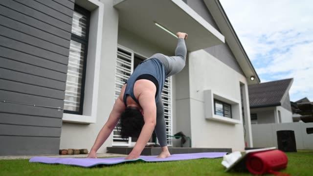 vidéos et rushes de femme asiatique d'adulte moyen chinois pratiquant la cour avant de yoga du matin de maison - stabilité