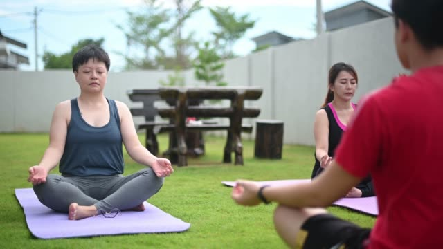 asian chinese mid adult woman practicing yoga front yard of house morning with friends - 40 49 years stock videos & royalty-free footage