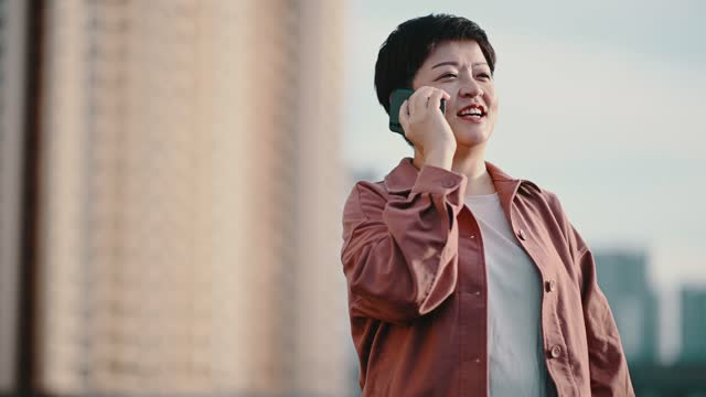 asian chinese mid adult woman smiling at outdoor during evening talking over the phone - satisfaction stock videos & royalty-free footage