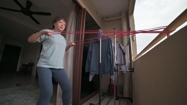 vidéos et rushes de femme mi-adulte chinoise asiatique utilisant l'entraînement à domicile de la bande de résistance au balcon - une seule femme d'âge moyen