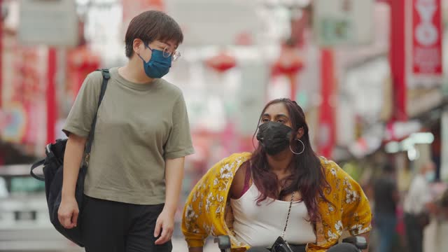 asian chinese mid adult woman with face mask walking side by side with her indian female friend with disability on wheelchair at city street - disability stock videos & royalty-free footage