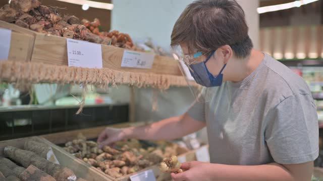 asian chinese mid adult woman with face shield face mask choosing ginger in greengrocer's shop - one mid adult woman only stock videos & royalty-free footage
