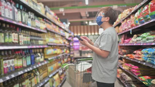 asian chinese mid adult woman with face shield face mask using smart phone at supermarket - one mid adult woman only stock videos & royalty-free footage