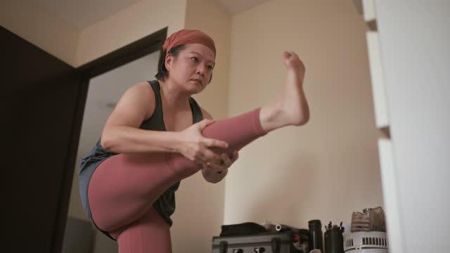vídeos y material grabado en eventos de stock de mujer asiática china mediana adulta con pañuelo en la cabeza practicando yoga en el dormitorio de su apartamento - una mujer de mediana edad solamente