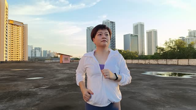 屋上駐車場n朝に走っているスポーツトラックスーツを持つアジアの中国の中年の大人の女性 - 女子トラック競技点の映像素材/bロール