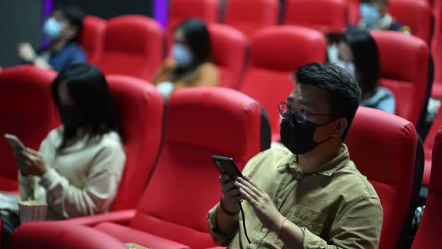 asian chinese mixed age group of people sitting in cinema waiting for movie showtime using smart phone - auditorium stock videos & royalty-free footage