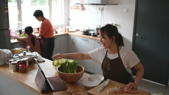 stockvideo's en b-roll-footage met aziatische chinese moeder koken bereiden voedsel aan de aanrecht en leren van internet met behulp van digitale tablet - chinese ethnicity