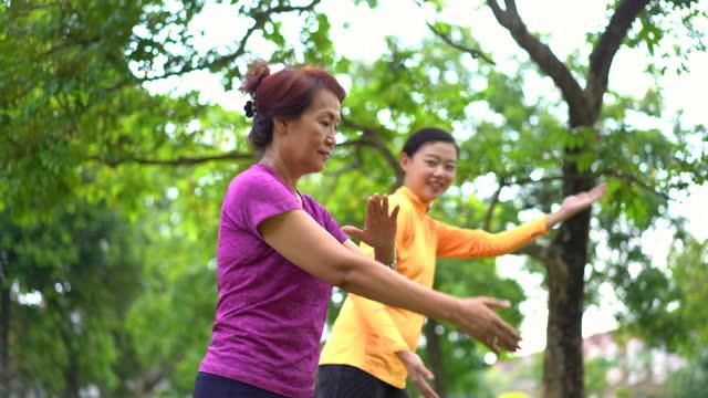 vidéos et rushes de fille chinoise asiatique de mère pratiquant le tai chi au stationnement public - famille avec un enfant