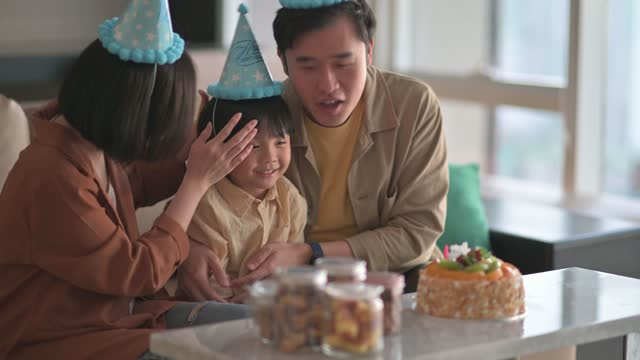 asian chinese mother wearing party hat for her son at home celebrating birthday getting ready for birthday celebration - party hat stock videos & royalty-free footage