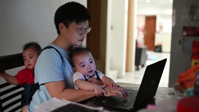 stockvideo's en b-roll-footage met aziatische chinese moeder met haar tweelingbaby's in slinger en babydrager terwijl het werken van huis gebruikend haar laptop in de keuken - tweeling