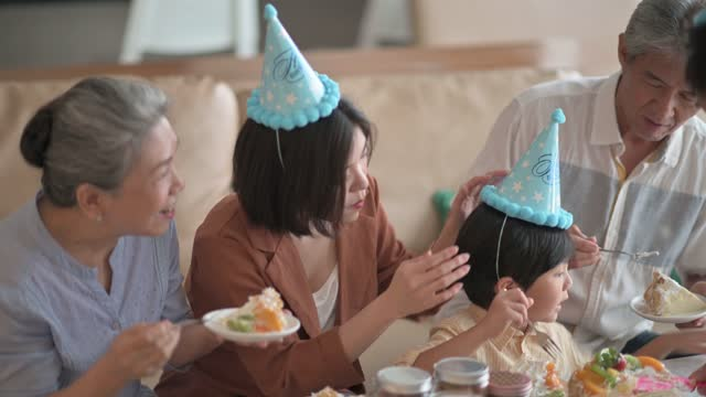 asian chinese multi generation family celebrating birthday with grandson wearing party hat eating birthday cake in living room - party hat stock videos & royalty-free footage