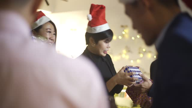 asian chinese office colleague exchange christmas present celebrating christmas party after working hour in office lounge - exchanging stock videos & royalty-free footage