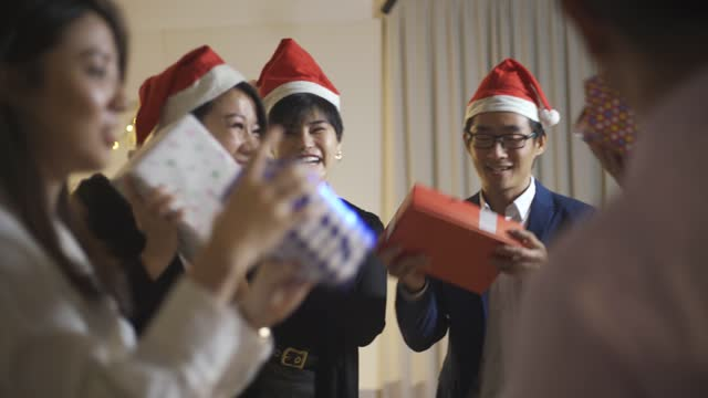 asian chinese office colleague exchange christmas present celebrating christmas party after working hour in office lounge - excitement stock videos & royalty-free footage