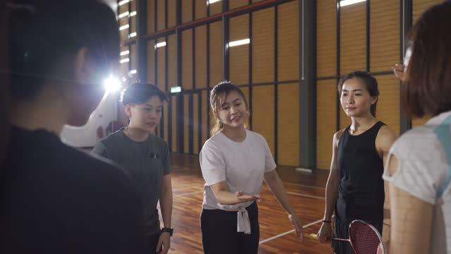 アジアの中国の審判とバドミントン選手は、バドミントンコートの側に決定頭や尾をひっくり返すためにコインを投げる - 女性選手点の映像素材/bロール
