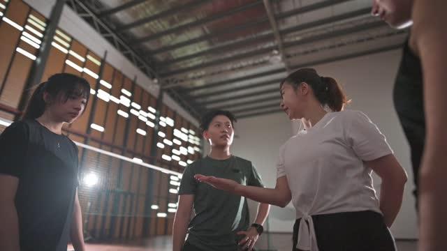 アジアの中国の審判とバドミントン選手は、バドミントンコートの側に決定頭や尾をひっくり返すためにコインを投げる - コイントス点の映像素材/bロール