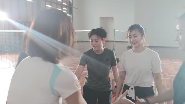アジアの中国の審判とバドミントン選手は、バドミントンコートの側を決定する頭や尾をひっくり返すためにコインを投げる - コイントス点の映像素材/bロール