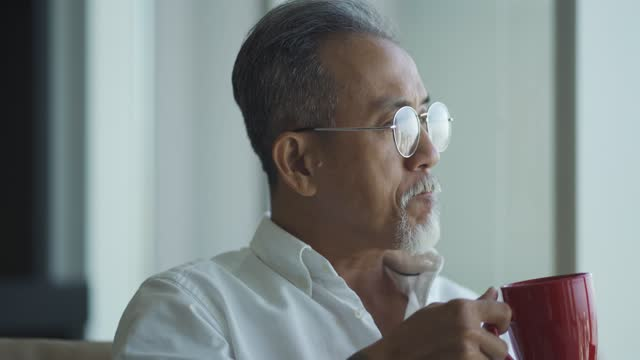 asian chinese retired senior man sitting relaxing at living room looking outside the window - looking away stock videos & royalty-free footage
