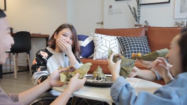vídeos y material grabado en eventos de stock de compañeros de cuarto asiáticos chinos comiendo albóndigas y charlando en casa - comida china